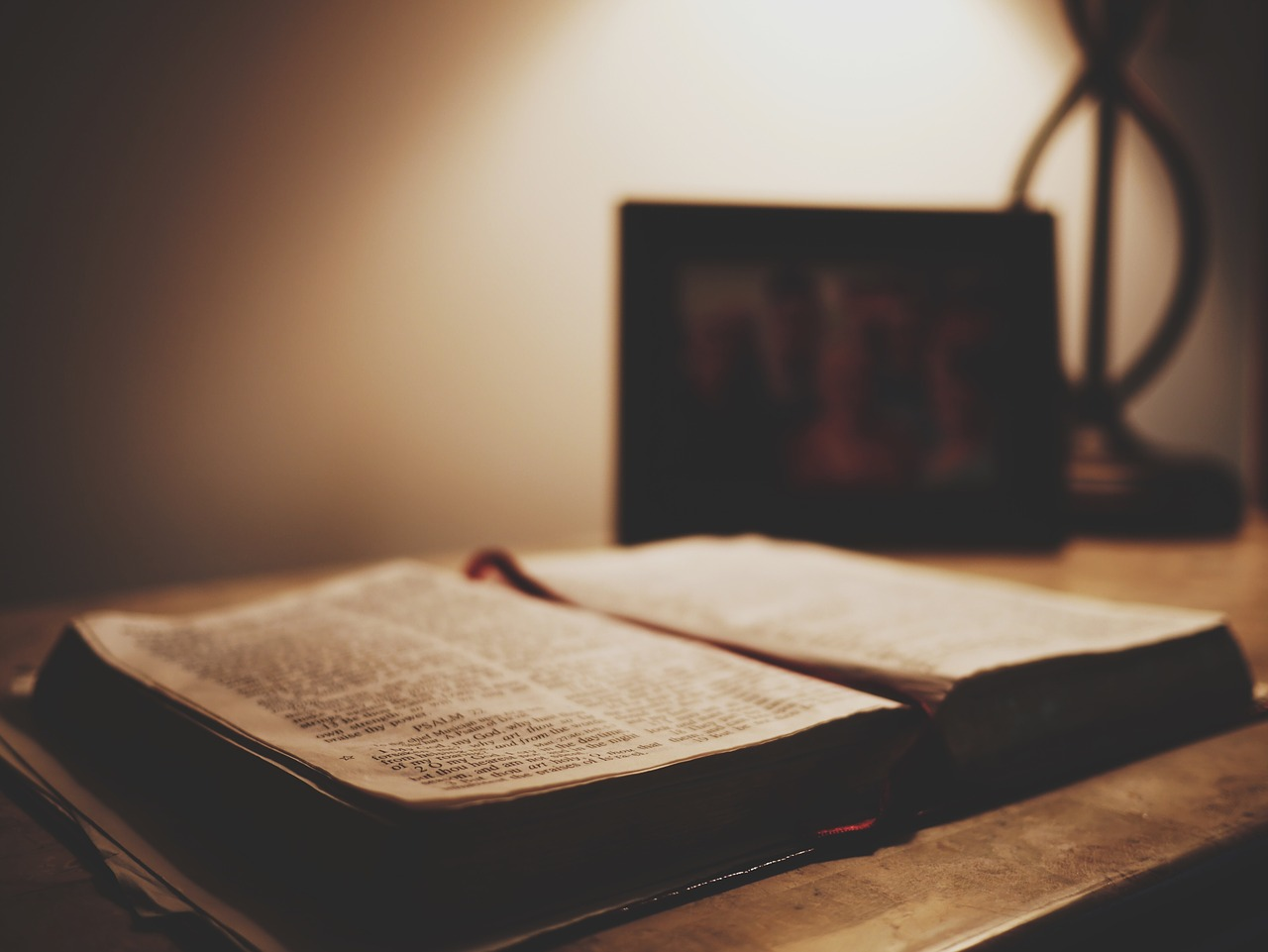 open bible on desk in dark room