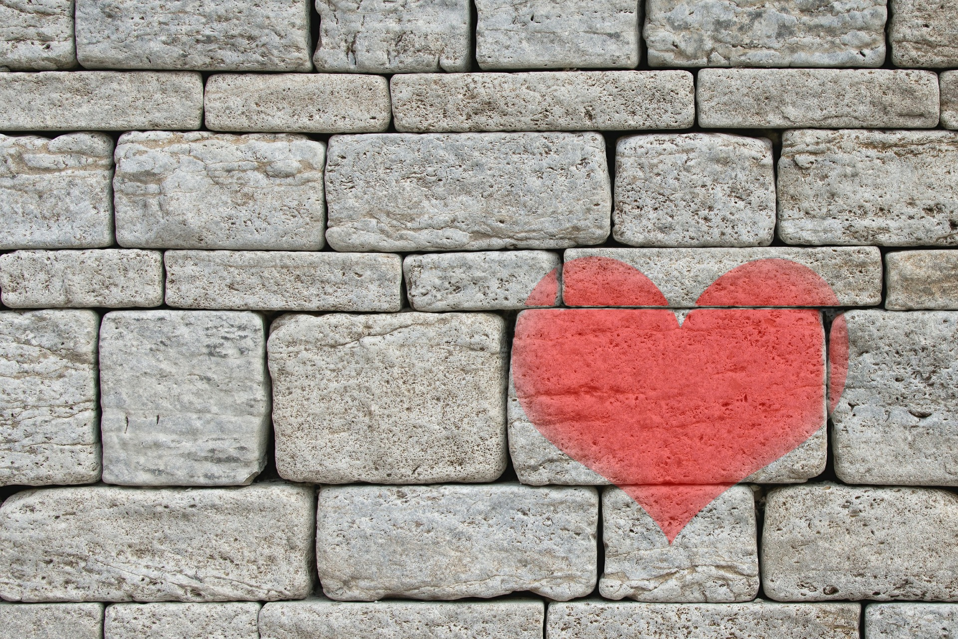 a stone faced brick wall with a red heart painted on it