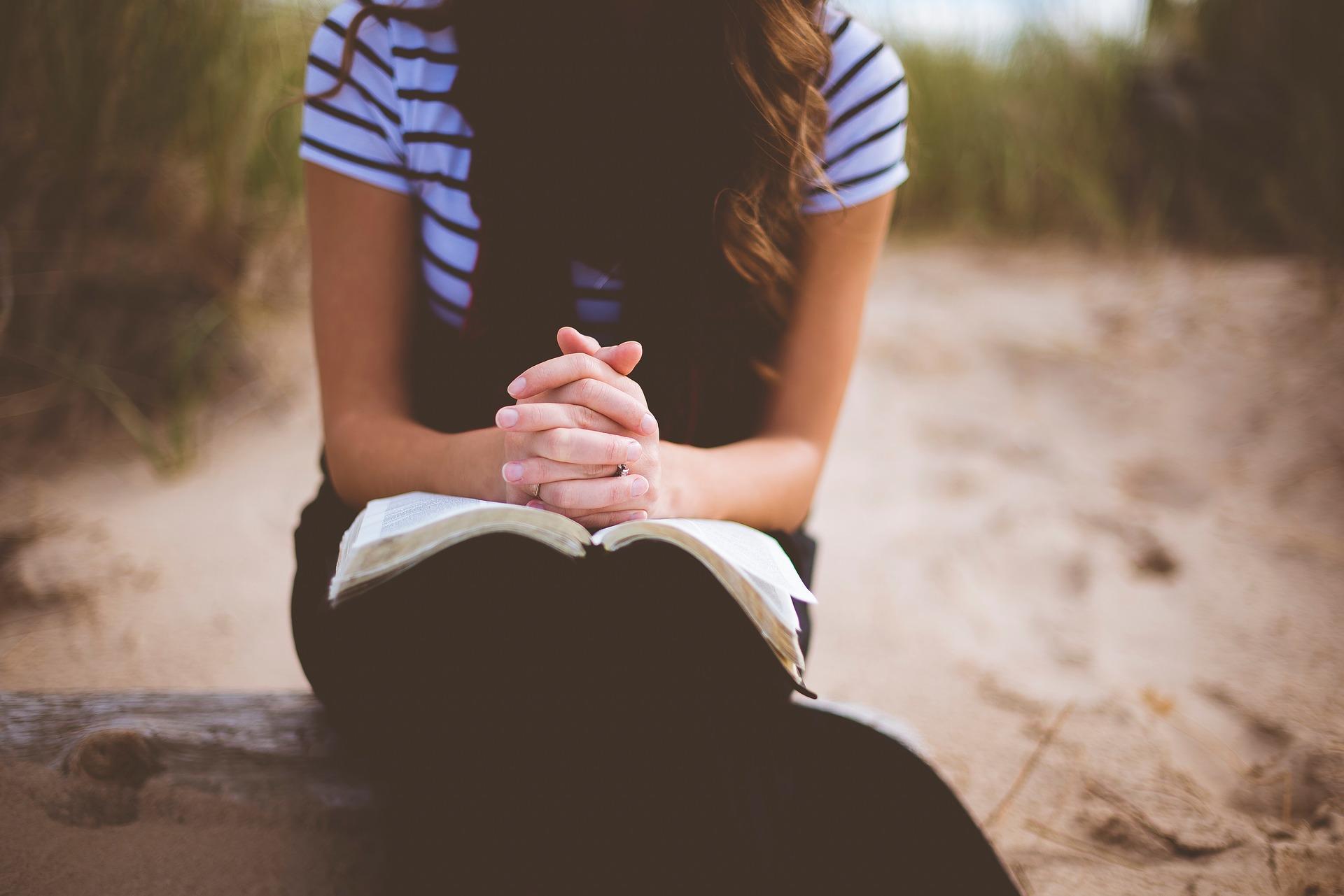girl folded hands on Bible