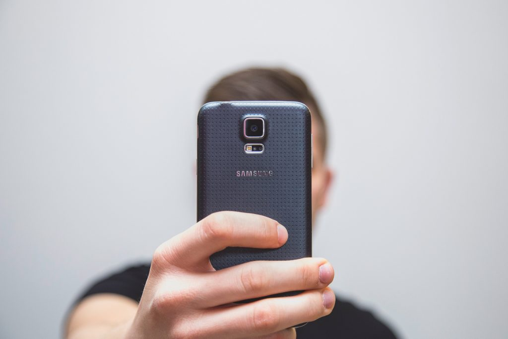 Man holding a phone in front of his face to take a selfie