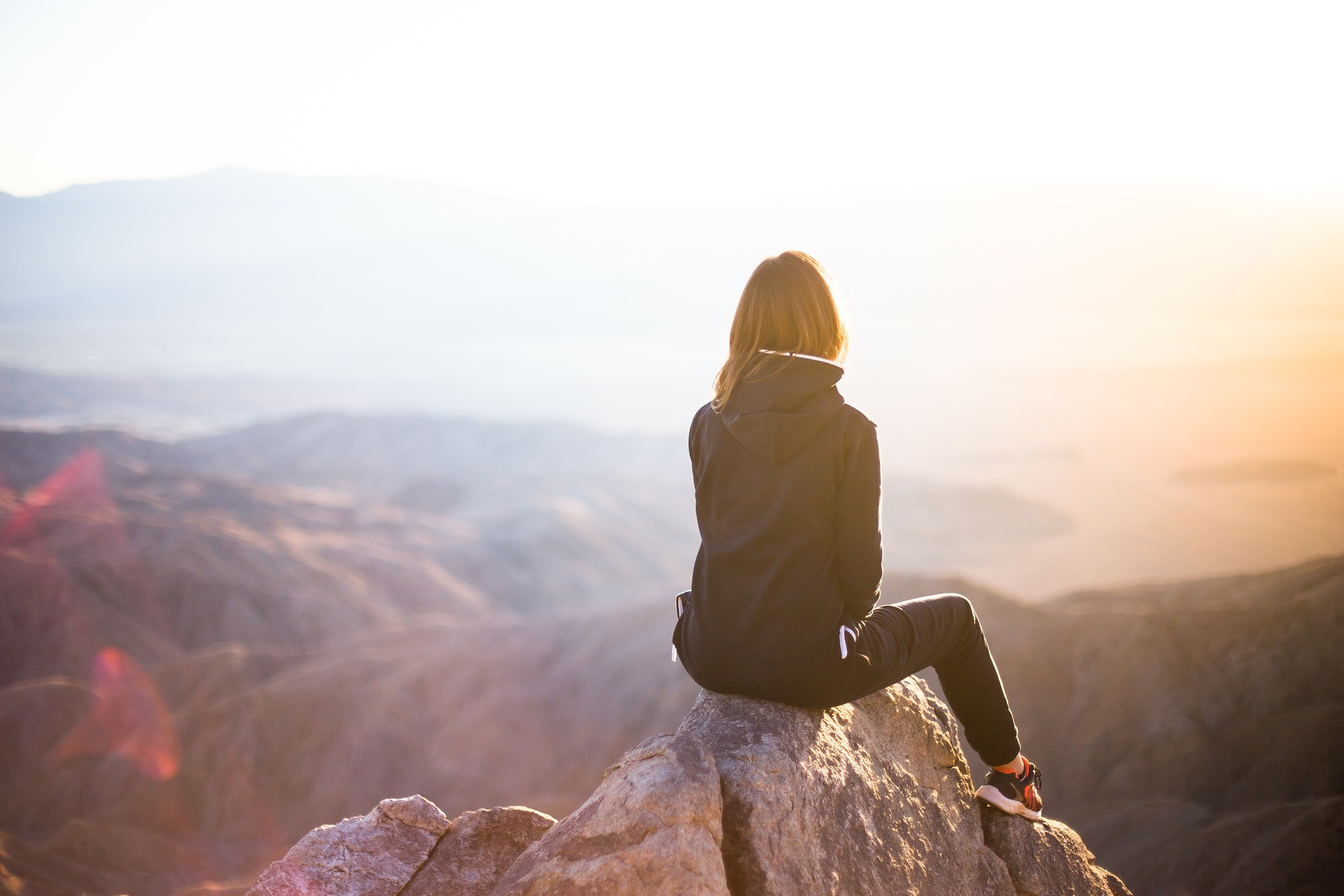 Woman sitting on top of mountain looking out over the landscape